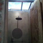 Overhead shower design. Body bath and towel provided.