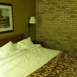 King bed with art and brick and textured wallpaper walls