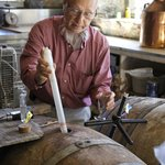 Warren using a wine thief to take a sample from a barrel.