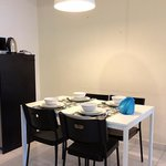 Dining area with complete sets of cutleries. Fridge, kettle & microwave oven on the left.
