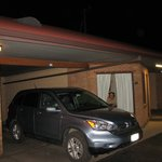 The car parked partially under the carport