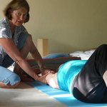 Nancy adjusting student in yoga.
