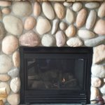River-stone surrounded gas fireplace