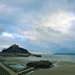 View from the balcony rooms to St Michael's Mount on a cloudy day at low tide.