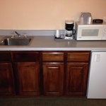 Counter with sink/coffee maker/fridge/microwave counter. On left is bathroom, on right are hange