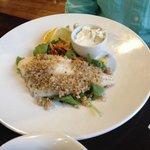 White fish on a bed of salad greens. Came with a side of green peas and two baked potatoes. The