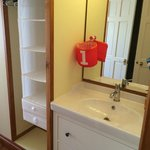 Storage and modern sink and mirror. Toilet and shower en suite