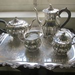 a silver tea service on display in museum