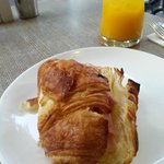 Ham and cheese croissant and orange juice.  I love the bent glass!