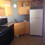 Oven, dishwasher, sink, full size refrigerator, wine rack, coffee mugs, plates, bowls, & ice buc