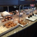 Croissants, rolls, pastries, muffins, and cake at the breakfast buffet.