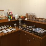 Tea, fruit, preserves, Nutella, cereal, and yogurt at the breakfast buffet.