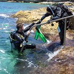 Steve helping a diver out of the water by grabbing fins