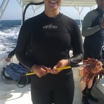 Dive Master Amber catching a Lion Fish for an eel's lunch
