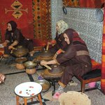 Women grinding the nuts to make oil