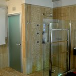 Open shower and glass toilet room door
