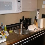 Kitchen: microwave, stove top, sink, coffee maker, fridge, utensils