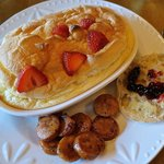 Orange omelet soufflé with strawberries, chicken sausage, English muffin and huckleberry preser