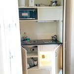 Kitchenette with fridge, hob, microwave, kettle, sink.