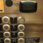 Place the room key by the black sensor and then select the floor in the elevator.
