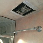 Hole in ceiling and exposed light fixture in bathroom.
