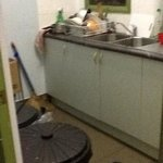 kitchen with oily dishes and full trash cans