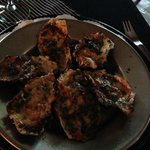 Oysters with spinach, bacon, and parmesan cheese.