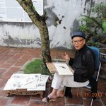 An artist draws in the verandah of the Dinh Kim Ngyan communal house
