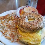 everything bagel breakfast sandwich with hash browns and fruit