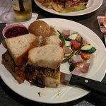 Meat loaf sandwich with mash potatoes, brown gravy, cranberry sauce and veggies