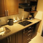 Kitchenette includes induction cooktop, microwave, fridge, and bar sink