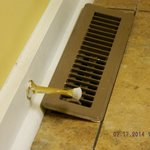 The floor vent not cut out to lay flat leans against molding