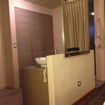 Open bathroom of the Deluxe room. Two sinks in the middle. The toilet is on the left and the sho