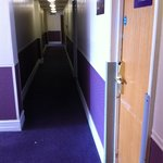 Purple hallway with damaged doors & trim in need of paint.