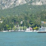 Photo of the hotel [set amongst the trees] viewed from Garda looking back across the lake.