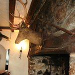 Pikes and deer's head over the fireplace.