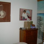 The bedroom with dresser and art