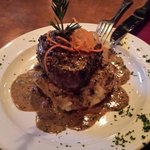 Lobster stuffed filet mignon served over bacon mashed potatoes topped with whiskey peppercorn sa