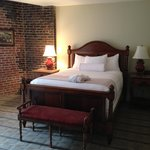 The queen bed in our room with exposed brick wall.