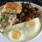 Sausage gravy over a cheddar scallion biscuit, eggs and home fries
