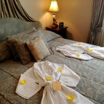 bed with robes and fresh rose petals