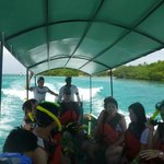 Boat that takes people to snorkeling site and our guides in back. (Hard working guys)