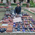 Friendly man selling slippers and leather goods in the courtyard