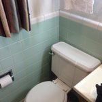 Cute original tilework and fixture in the bathroom add historic character.  The toilet was dated