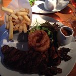 Sirloin Steak with peppercorn sauce, onion rings, mushrooms, tomato & chips