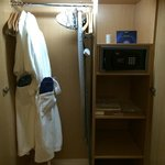Bathrobes, ironing board and safe in closet.