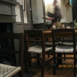 Busy waiter breezing through the dining area; traditional furnishings for diners