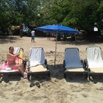 Beach with hotel chairs, umbrella, and towels