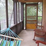 screened in porch with hammock and chairs