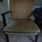 a tatty and stained chair in the bedroom
